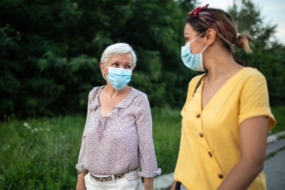 Senior walking with caregiver, both wearing masks