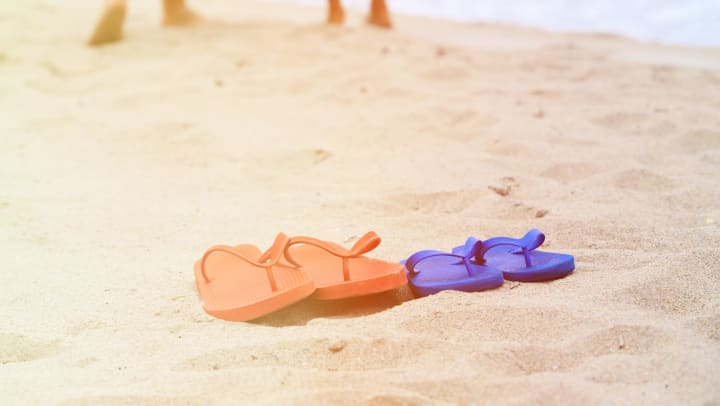 One pair of red sandals and one pair of blue sandals on a sandy beach with two pairs of legs in the background