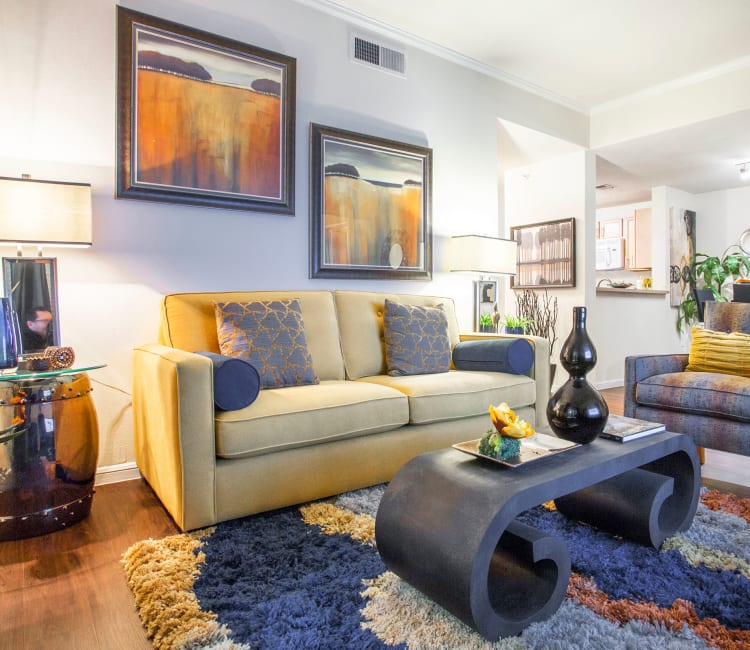 Living area with hardwood floors in a model home at Riata Austin in Austin, Texas