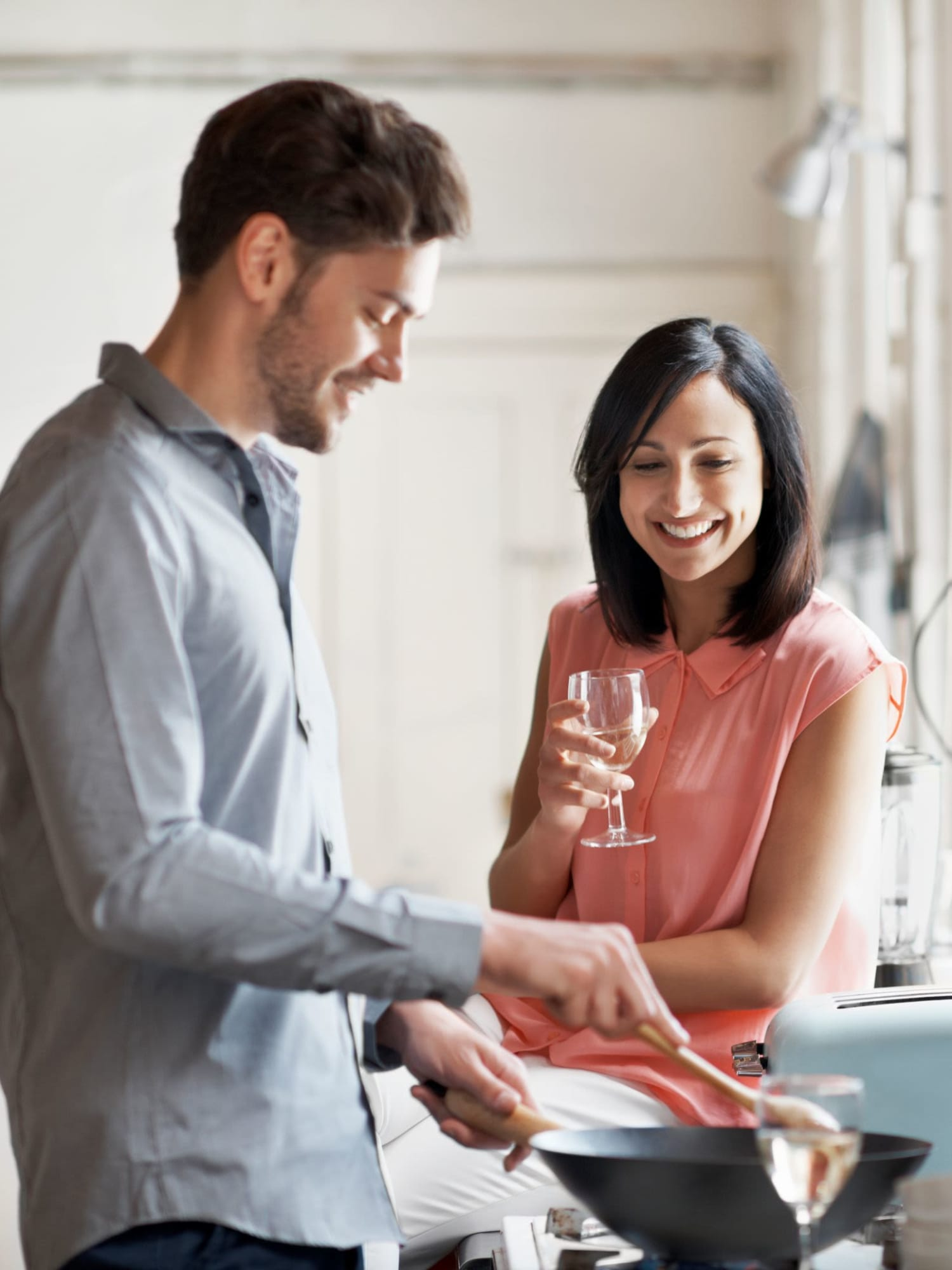 Happy resident couple cooking and enjoying a glass of wine in their kitchen at Lakeside Landing Apartments in Lakeside Park, Kentucky