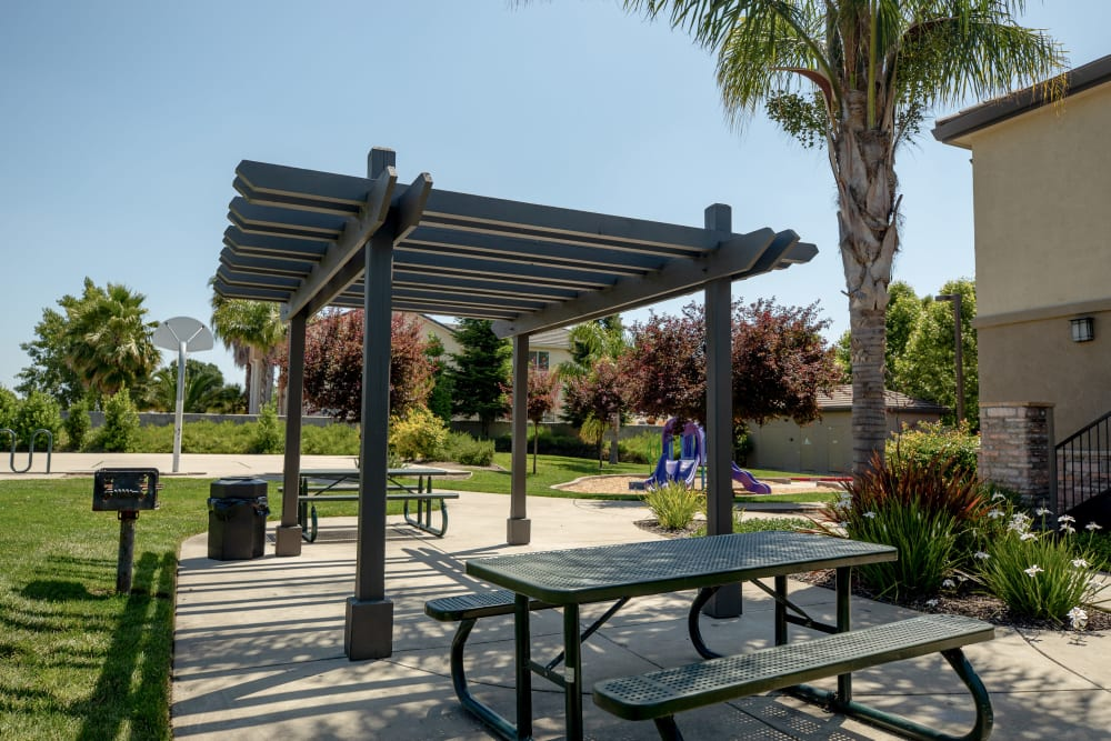 Outdoor picnic area next to a playground at Wolf Ranch Condominium Rentals in Sacramento, California