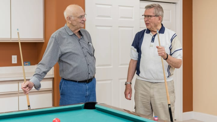 Image of two male Touchmark residents playing pool in the billiards room.