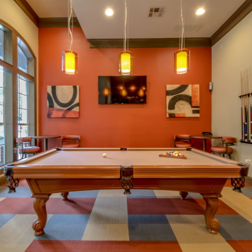 Community billiards room with a large window for natural light at Alon at Castle Hills in San Antonio, Texas