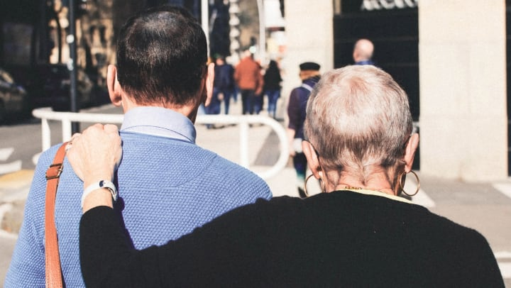 senior couple walking together across a crosswalk