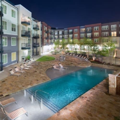 Resort-style swimming pool area in the early evening at Union At Carrollton Square in Carrollton, Texas