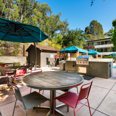 Overhead view of an umbrella partially shading a table and chairs at Sofi Belmont Glen in Belmont, California