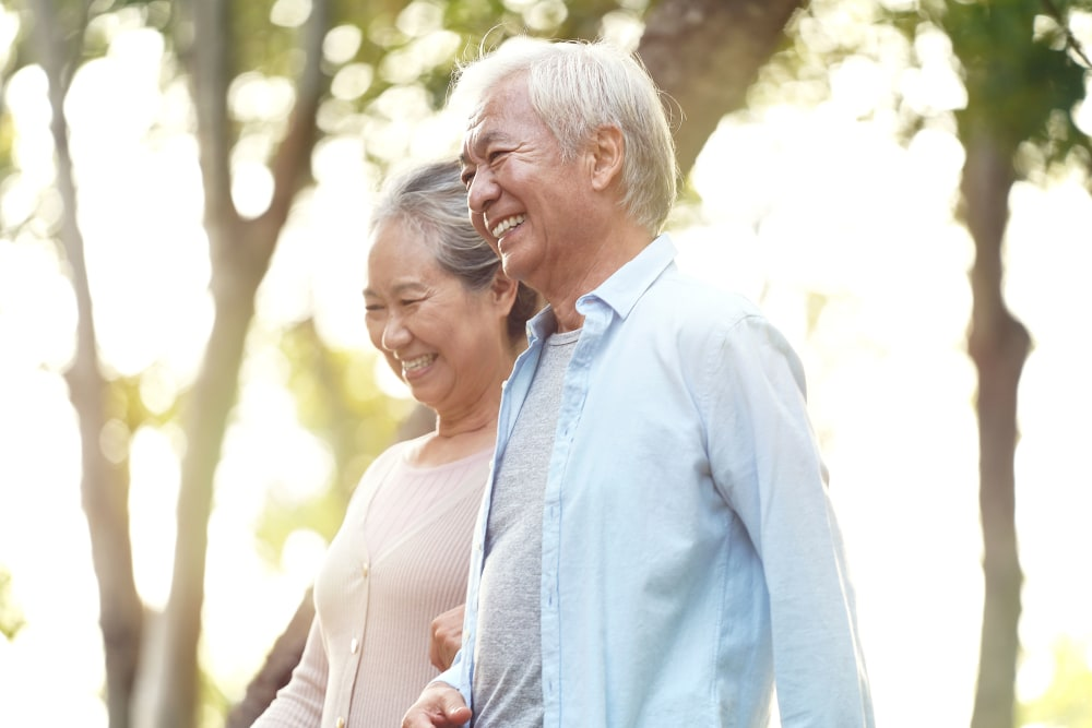 Couple smiling and walking outside at Merrill Gardens at Siena Hills in Henderson, Nevada