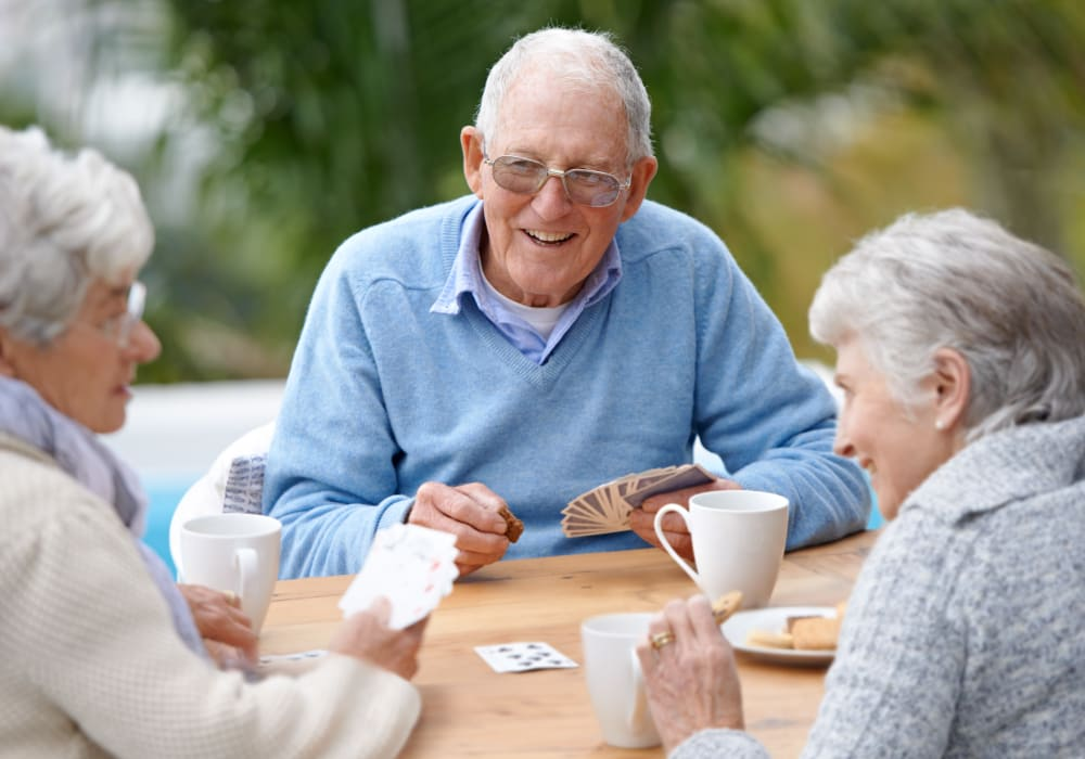 Resident playing cards with other residents at Clayton Oaks Living in Richmond, Texas