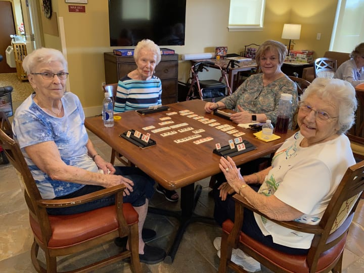 The Groves residents gather around a table and play their favorite game!