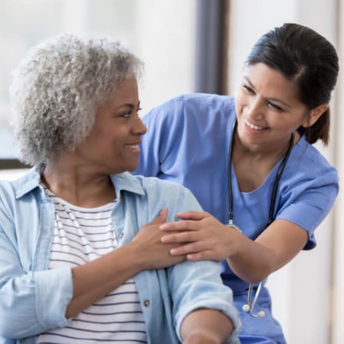 A nurse holding a resident's hand at Harmony at Harts Run in Glenshaw, Pennsylvania
