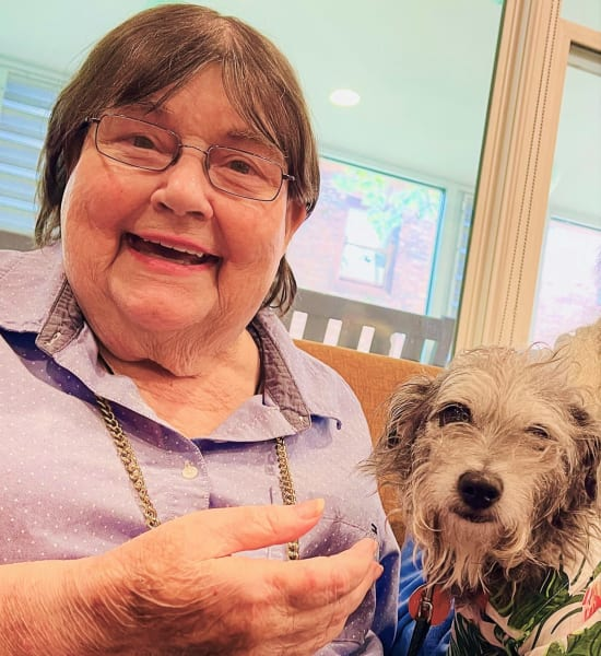A woman smiles with a small therapy dog in her lap