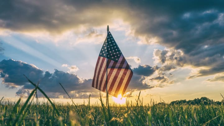 American flag flying over a grassy plain, with sunlit clouds in the background