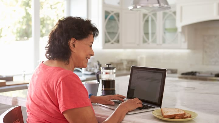Woman works on computer in kitchen