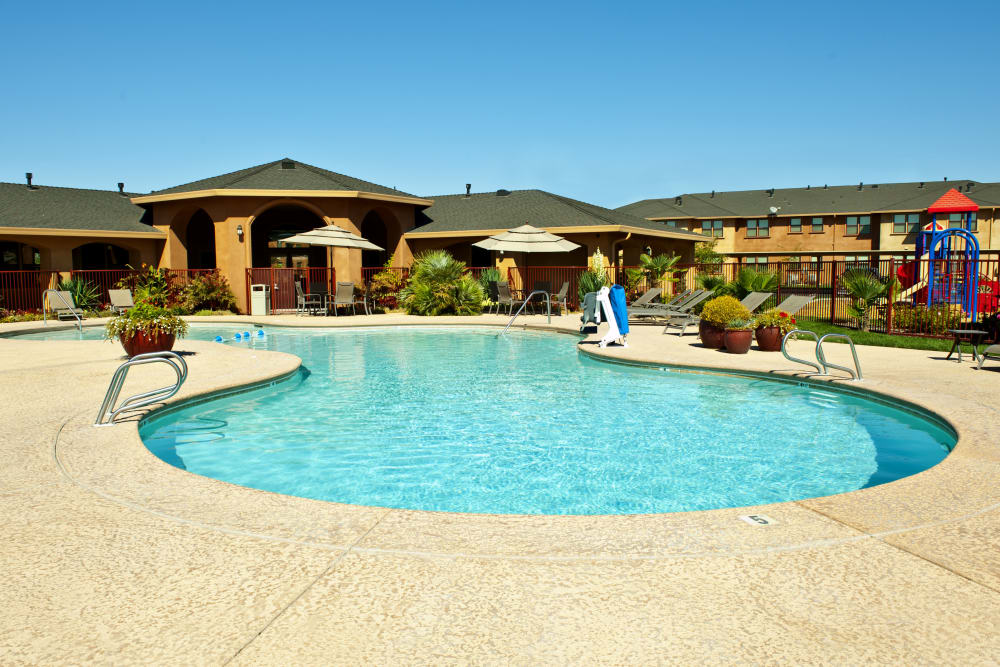 Swimming pool with covered seating and a playground at Villa Risa Apartments in Chico, California