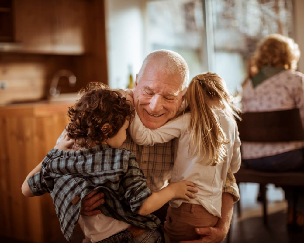 A resident hugging his grandchildren at Western Slope Memory Care in Grand Junction, Colorado