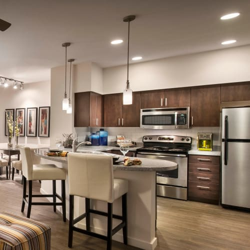 Gourmet kitchen with an island and granite countertops in a model home at Redstone at SanTan Village in Gilbert, Arizona