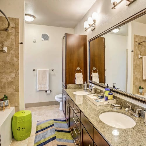 Dual sinks and a beautiful granite countertop in a model home's master bathroom at Sundance Creek in Midland, Texas