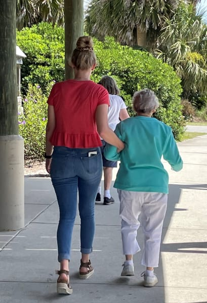 One Carolina Park (SC) team member helps one of the residents walk down the boardwalk,