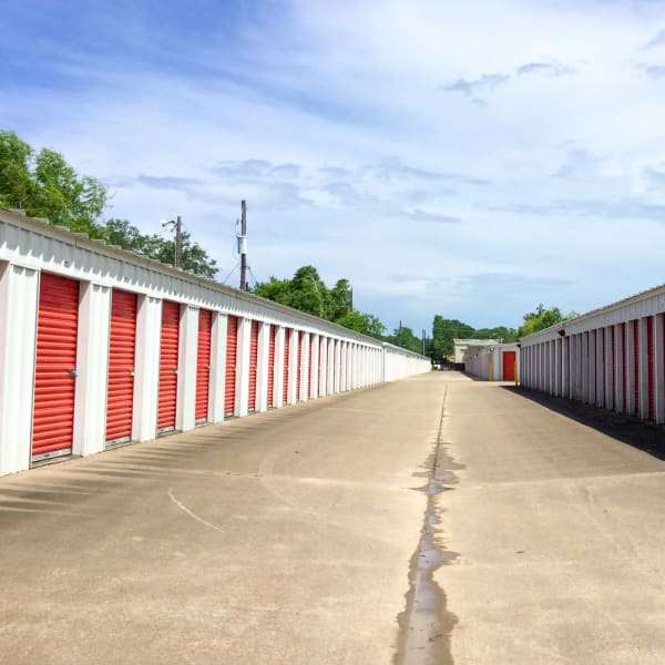 Exterior units with red doors at StorQuest Self Storage in Friendswood, Texas