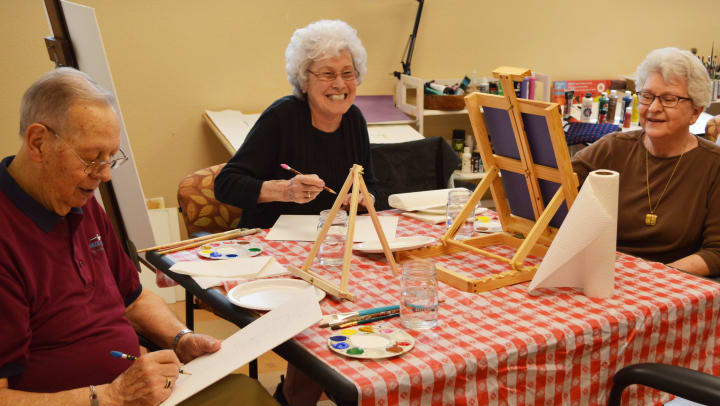 Image of three Touchmark residents smiling as they paint on easels together.