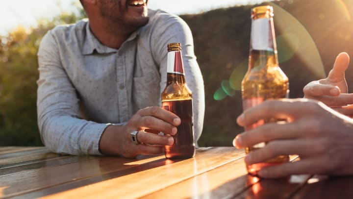 Two men sitting outdoors at a wooden table having beers and talking.