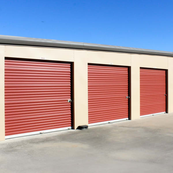 Outdoor storage units with red doors at StorQuest Self Storage in Kyle, Texas