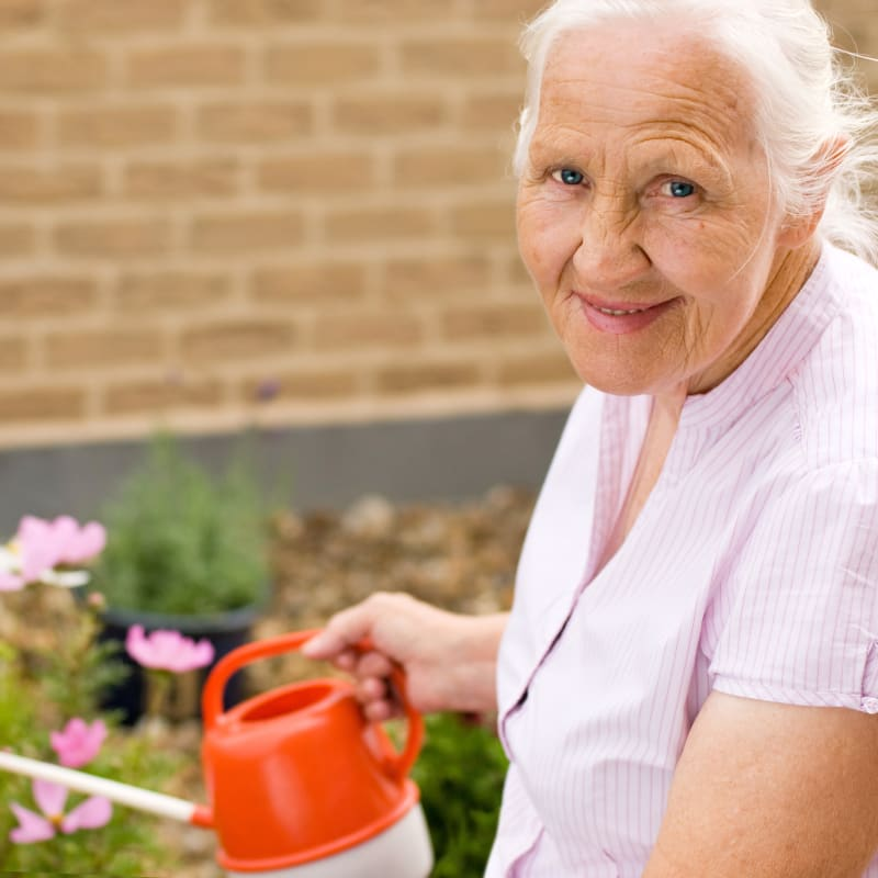 Resident watering plants outside at The Hearth at Hendersonville in Hendersonville, Tennessee