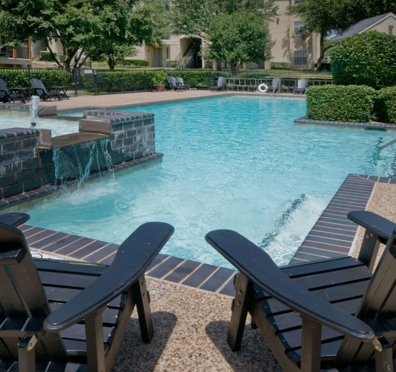 Chaise lounge chairs and a fountain near the pool at Rockbrook Creek in Lewisville, Texas