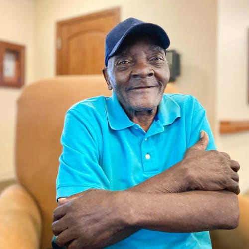 A resident walking smiling and hugging himself at Oxford Glen Memory Care at Carrollton in Carrollton, Texas