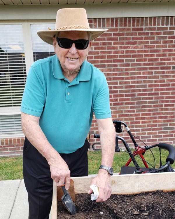 A gentleman gardening in a planter box at Trilogy Health Services in Louisville, Kentucky