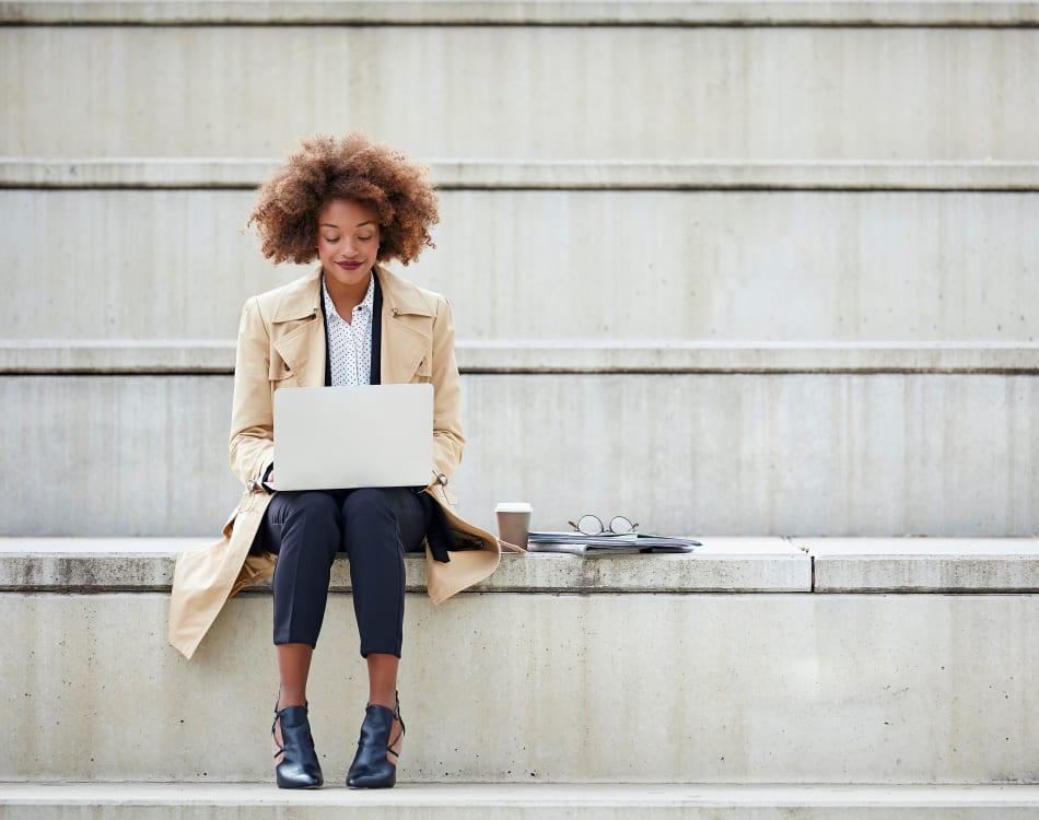 Resident student doing some homework on her laptop near Sofi at Salem Station in Salem, Massachusetts