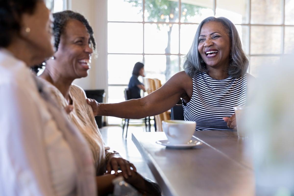 Resident enjoying coffee with family members at Monark Grove Clarkston in Clarkston, Michigan