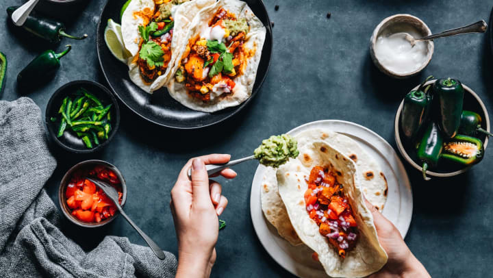 Hands preparing a taco with a tortilla in one hand and a spoonful of guacamole in the other, surrounded by an array of ingredients in small bowls.