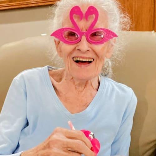 Resident in flamingo glasses at Glen Carr House Memory Care in Derby, Kansas