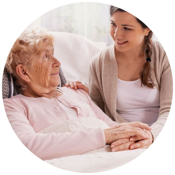 Resident in a bed talking to a young person at a Ebenezer Senior Living community
