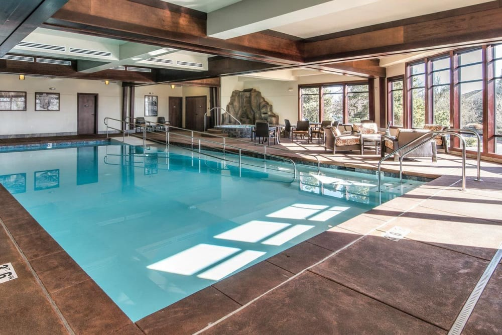 Sun shines into gorgeous indoor pool area with plenty of relaxation space at The Springs at Carman Oaks in Lake Oswego, Oregon