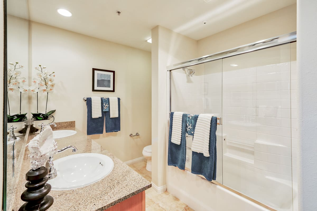 Bathroom with granite countertop, double sinks and shower at The Villa at Marina Harbor in Marina del Rey, California