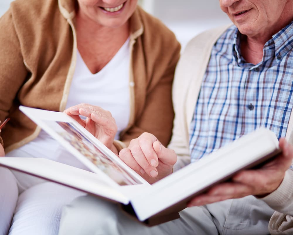 Senior couple looking at photo album at Western Slope Memory Care in Grand Junction, Colorado