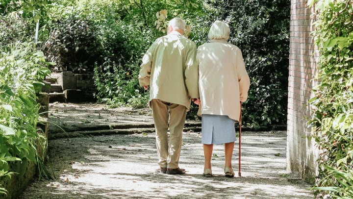 senior couple going on a walk together through the park