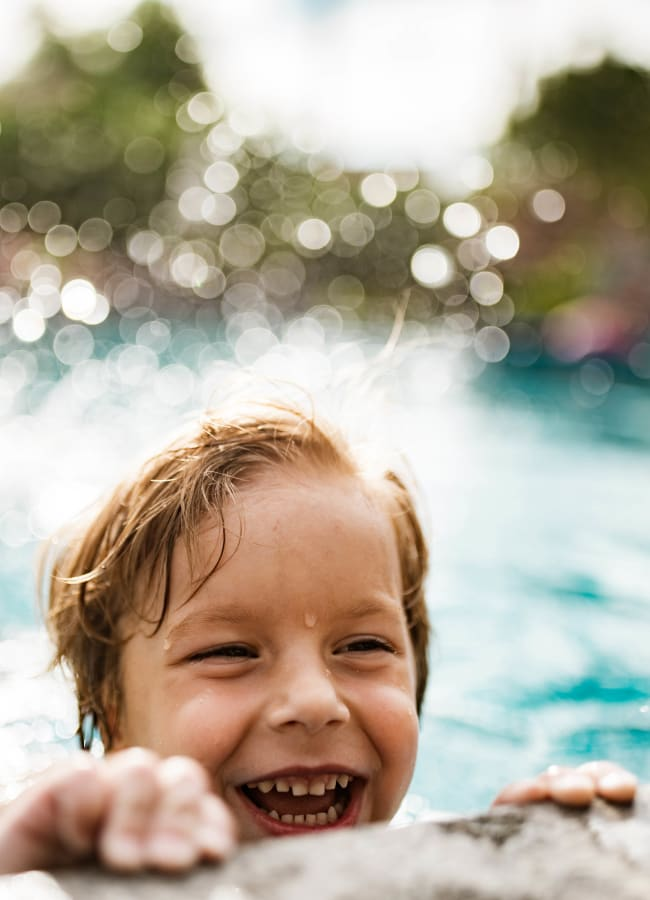 Resident child having a blast in the pool at Alize at Aliso Viejo Apartment Homes in Aliso Viejo, California