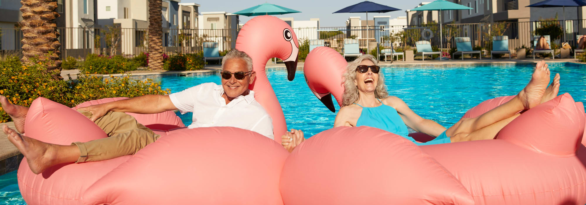 Residents on flamingo pool floats at Las Casas at Windrose in Litchfield Park, Arizona