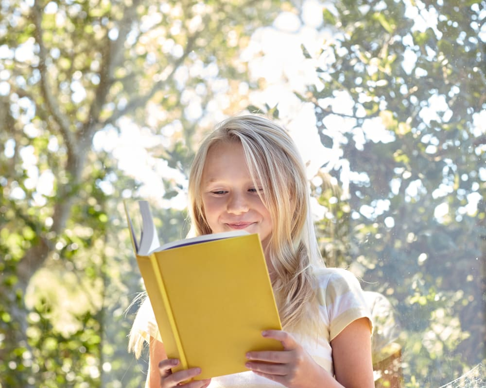 Child happily reading a book in her new home at Sofi at Somerset in Bellevue, Washington