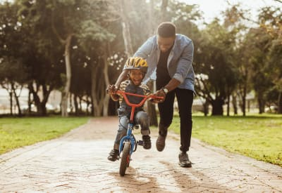 Resident father teaching his son to ride a bike after school near their home at Ten 30 and 49 Apartments in Broomfield, Colorado