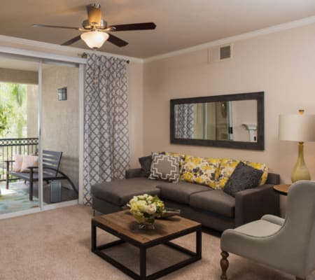 Spacious living room with balcony access at Alize at Aliso Viejo Apartment Homes in Aliso Viejo, California