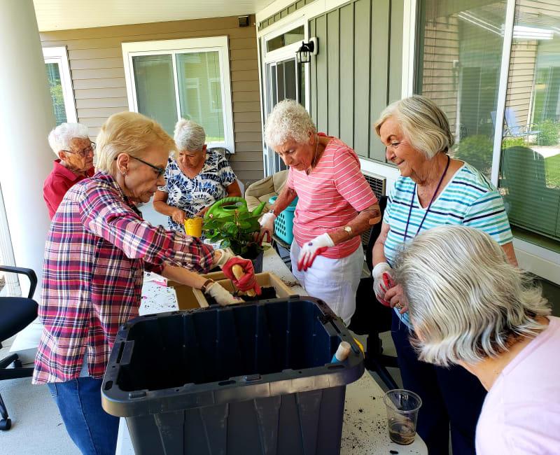 Residents planting flowers outside at Arbor Glen Senior Living in Lake Elmo, Minnesota