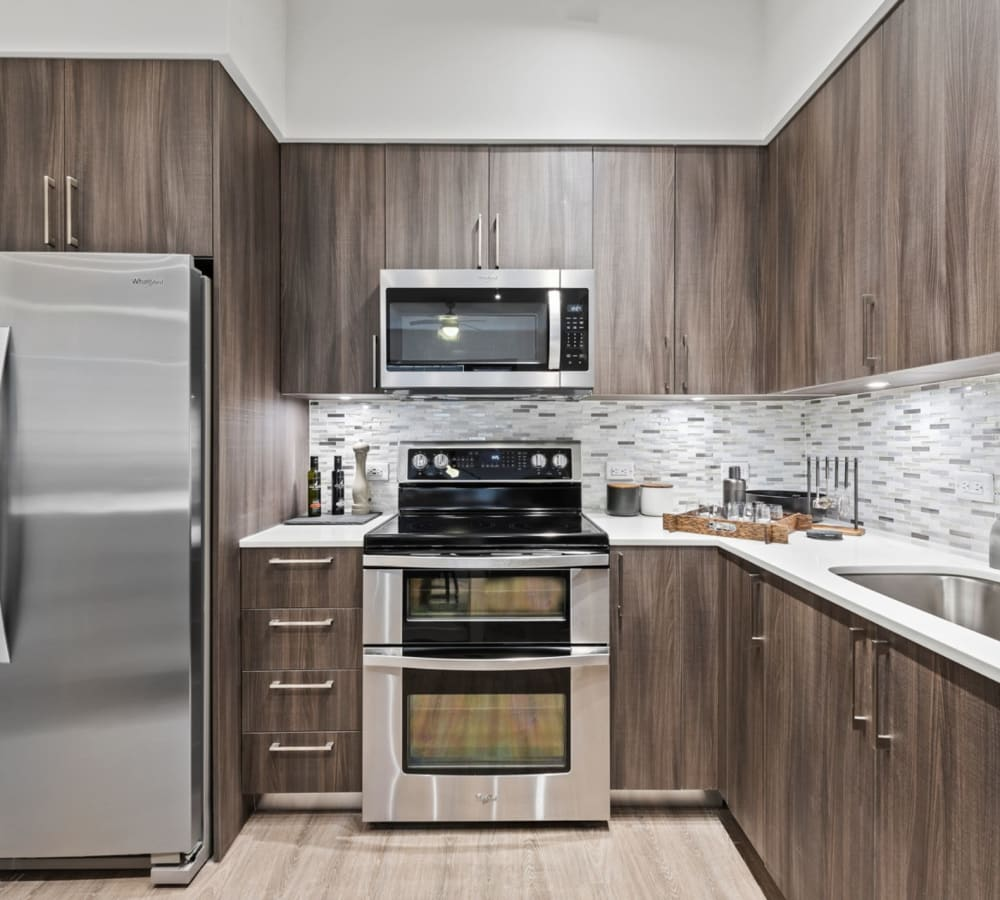 Kitchen with dark wood cabinets and stainless steel appliances at 6600 Main in Miami Lakes, Florida