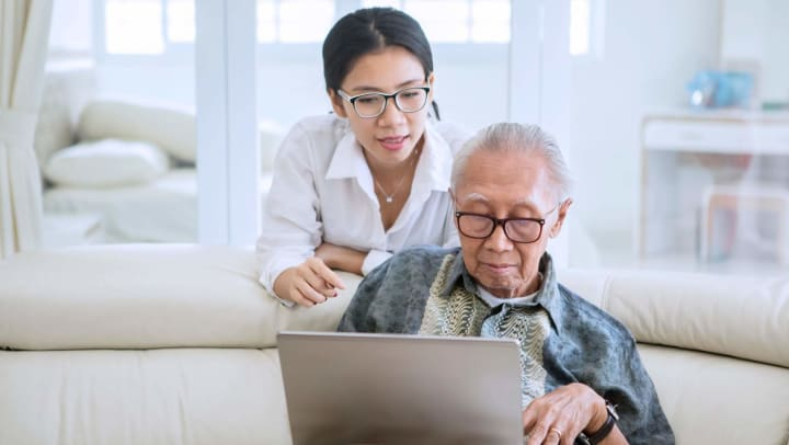 Senior man looking at lap top with daughter