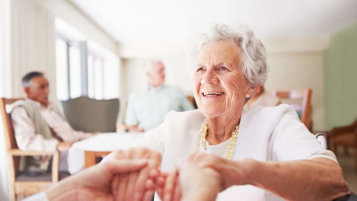 Senior woman holding hands with someone off camera