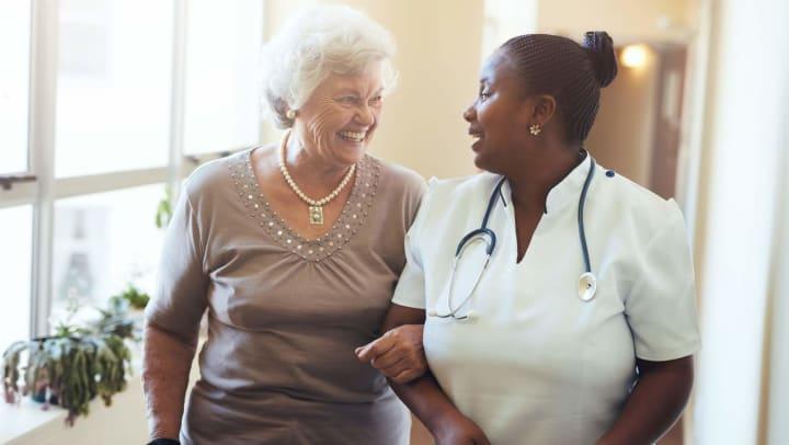 Senior woman walking with nurse