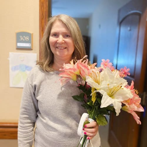 Resident holding flowers and smiling at Oxford Glen Memory Care at Carrollton in Carrollton, Texas